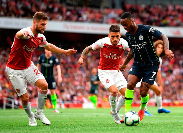 Raheem Sterling of Manchester City runs with the ball under pressure from Shkodran Mustafi of Arsenal and Lucas Torreira of Arsenal.