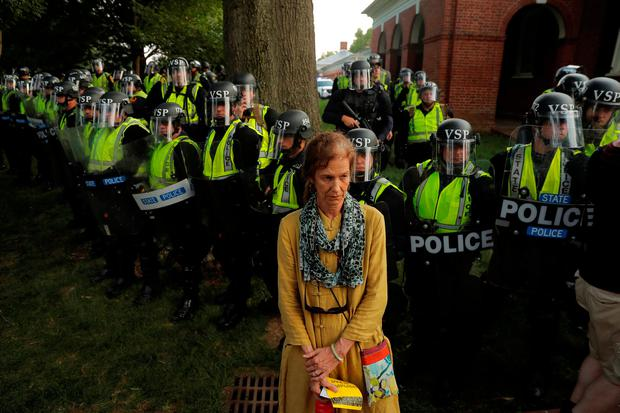 A counter-protester stands in front of state police at the University of Virginia in Charlottesville