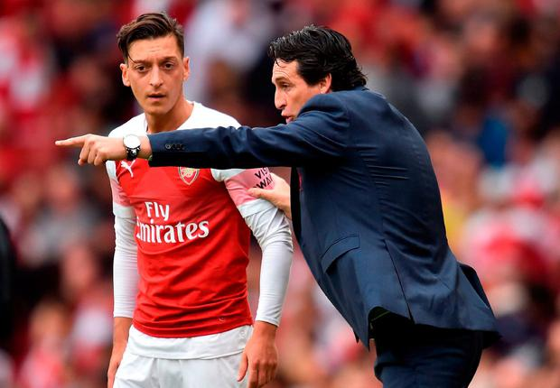 Unai Emery gives some instructions to Mesut Ozil. Photo: Glyn Kirk / AFP