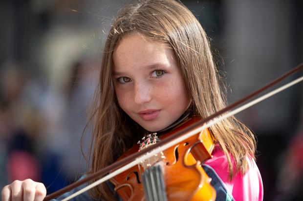 Caoimhe Hegarty (10) from Cong, Co Mayo, entertains the crowds on the first day of the Fleadh Cheoil na hÉireann yesterday. For the first time in its 67-year history, Fleadh Cheoil has arrived in Ireland's largest town, Drogheda, Co Louth. The family friendly festival will bring an injection of around €40m to the local economy. Photo: Ciara Wilkinson