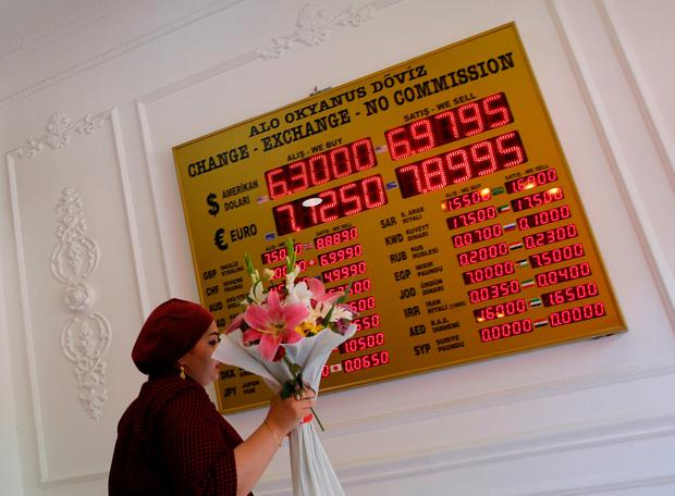 A woman walks past by a board showing exchange rates in a currency exchange office in Istanbul. Photo: Reuters