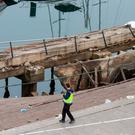 A police officer photographs the collapsed boardwalk in Vigo. Image: AP photo