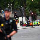 Armed police stand in the street after a car crashed outside the Houses of Parliament in Westminster, London, Britain, August 14, 2018. REUTERS/Hannah McKay