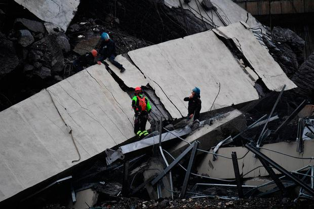 Rescues work among the debris of the collapsed Morandi highway bridge in Genoa, Tuesday, Aug. 14, 2018. (Luca Zennaro/ANSA via AP)