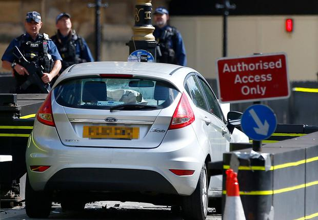 Armed police at the site after a car crashed outside the Houses of Parliament in Westminster, London. Photo: Henry Nicholls/Reuters