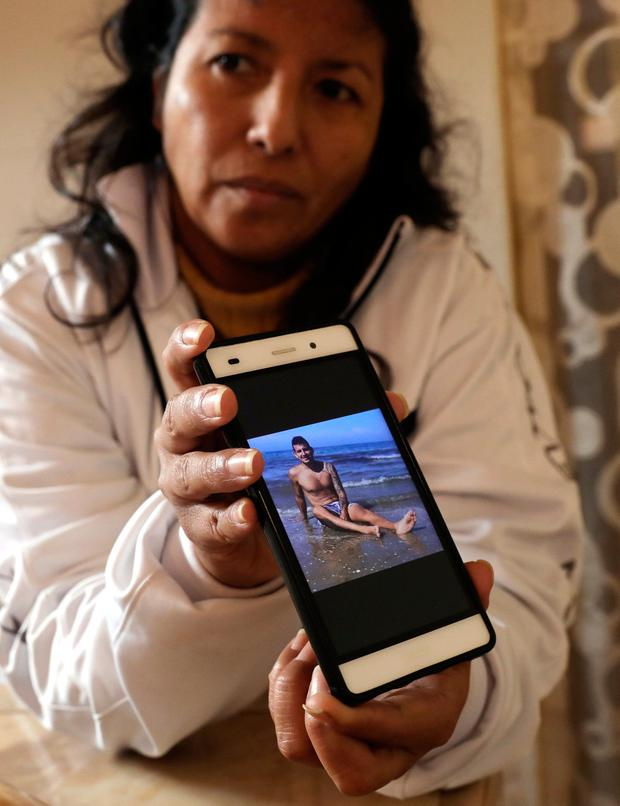 Relatives of Carlos Erazo, a Peruvian victim of Italian bridge collapse show a picture of him at their home in Callao, Peru, August 15, 2018. REUTERS/Mariana Bazo