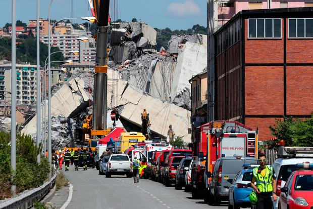 Firefighters and rescue workers stand at the site of the collapsed Morandi bridge in the port city of Genoa. Photo: Reuters