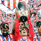 Atletico's Antoine Griezmann lifts the trophy