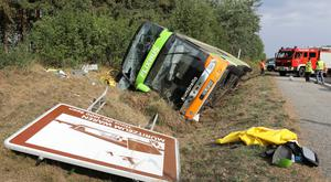 Sixteen people were injured when a bus struck a ditch and turned over (Bernd Wuestneck/dpa via AP)