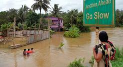 An Indian woman watches residents walking through flood streets next to their marooned houses on the outskirts of Kozhikode district, about 385 km north of Trivandrum in the south Indian state of Kerala. Photo: Getty Images