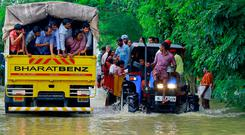 Flood affected people are rescued in a tractor, right as volunteers go for rescue work in a truck, left, at Kainakary in Alappuzha district, Kerala state, India (AP Photo/Tibin Augustine)