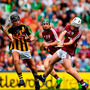 Seán McDonagh of Galway scores a point, while under pressure from Pádraig Dempsey of Kilkenny