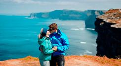 A German couple kiss during a walk along the Cliffs of Moher in Co Clare. Photo: Brian Arthur