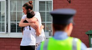 Leona Lambe (with back to camera) is consoled at the scene of the fatal stabbing of her father Gerard Fortune. Photo: Collins