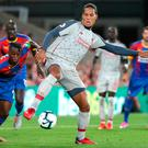 Virgil van Dijk of Liverpool controls the ball despite coming under pressure from Aaron Wan-Bissaka of Palace. Photo by Charlotte Wilson/Offside/Getty Images