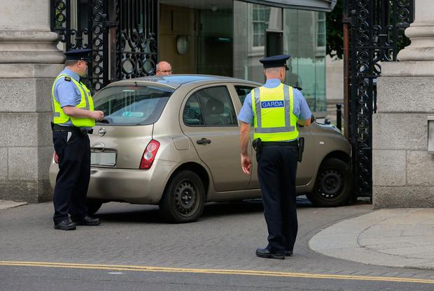 Gardaí inspects a car that crashed at the gates of government buildings in Dublin. Below: religious images seen in the car after the crash.