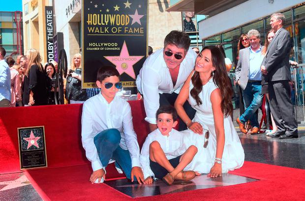 Television Producer Simon Cowell poses with his family on his Hollywood Walk of Fame Star at a ceremony in Hollywood, California, on August 22, 2018. (Photo by Frederic J. BROWN / AFP)FREDERIC J. BROWN/AFP/Getty Images