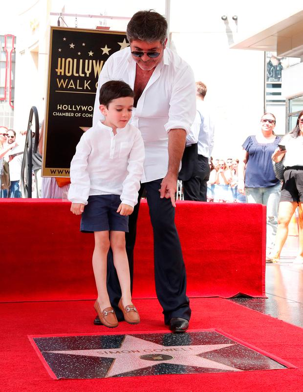 Television producer Simon Cowell and his son Eric pose on his star on the Hollywood Walk of Fame in Los Angeles, California, U.S., August 22, 2018. REUTERS/Mario Anzuoni