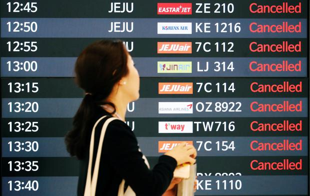 A woman walks past an electronic board that shows cancelled domestic flights due to Typhoon Soulik at Gimpo airport in Seoul, South Korea REUTERS/Kim Hong-Ji
