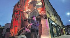 Artist Mantra with his mural during the Waterford Walls International Street Art Festival