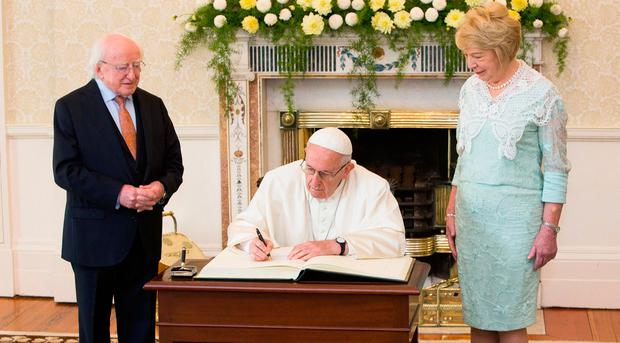 President Michael D Higgins, Pope Francis and Mrs. Sabina Higgins as he signs the visitors book at Áras an Uachtaráin. Photo: Maxwells