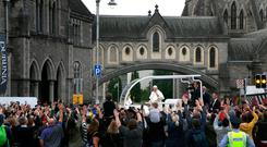 Pope Francis waves to the waiting crowds on Christchurch, Dublin as he travels in the Popemobile during his visit to Ireland. Photo: Brian Lawless/PA Wire