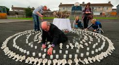 Aiden Corless lights candles in an artwork of clay children's shoes at the site of the former Tuam home for unmarried mothers in Co Galway yesterday. Photo: Niall Carson/PA