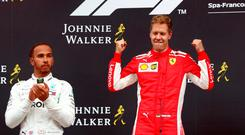 Ferrari's Sebastian Vettel celebrates on the podium after winning the race while Mercedes' Lewis Hamilton looks on. REUTERS/Francois Lenoir