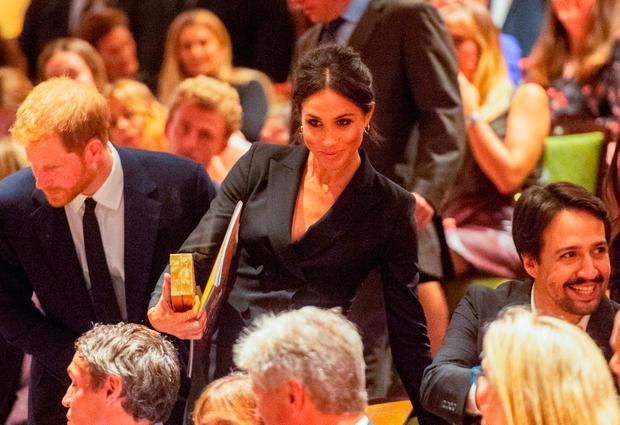 Britain's Prince Harry, Duke of Sussex (L) and Britain's Meghan, Duchess of Sussex (C) take their seats next to US composer and writer Lin-Manuel Miranda (R) at a gala performance of the musical 'Hamilton' in support of the charity Sentebale at the Victoria Palace Theatre in London on August 29, 2018. (Photo by Dan CHARITY / POOL / AFP)DAN CHARITY/AFP/Getty Images