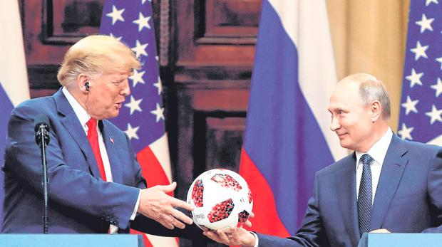 Political football: US President Donald Trump receives a football from Russian President Vladimir Putin at the now infamous meeting. Photo: Reuters