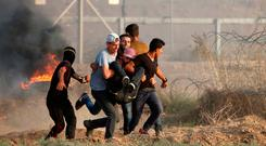 Palestinian demonstrators carry a wounded man yesterday during a protest, where Palestinians demanded the right to return to their homeland, at the border fence between Israel and Gaza, east of Gaza City. Photo: Reuters