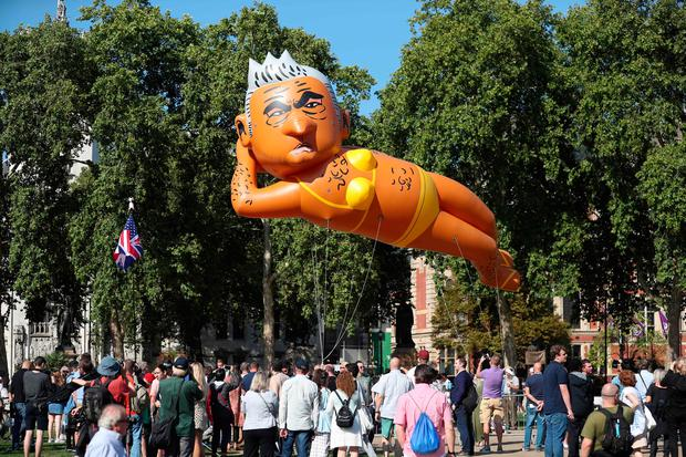 A large balloon depicting London Mayor Sadiq Khan in a yellow bikini floats above a small crowd of demonstrators in Westminster (Photo by Daniel LEAL-OLIVAS / AFP)DANIEL LEAL-OLIVAS/AFP/Getty Images