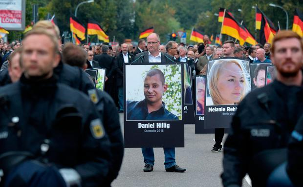 A protester holds a poster with a photo of a man killed a week earlier during a demonstration in Chemnitz, eastern Germany, Saturday, Sept. 1, 2018. AP Photo/Jens Meyer