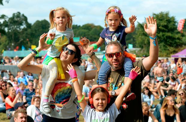 Family fun: Angela and Justin Moor, from Stradbally, carry twins Tara and Marianne (5) as oldest daughter Sienna (9) also gets in the Electric Picnic party spirit. Photo: Caroline Quinn