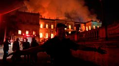 A police officer prevents people from getting near the building as a massive fire engulfs the National Museum in Rio de Janeiro on September 2, 2018. Photo: CARL DE SOUZA/AFP/Getty Images