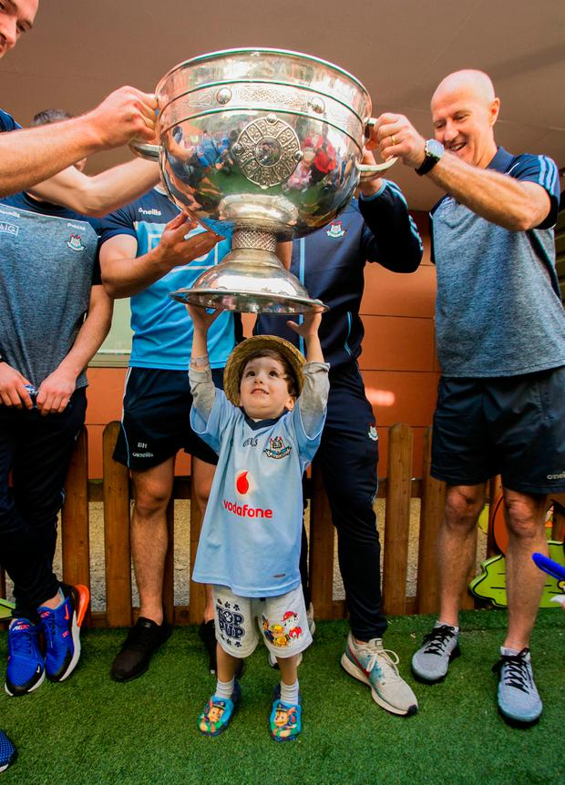 Jake Keegan (3), from Tallaght, lifts the Sam Maguire as the Dubs visit Our Lady's Children Hospital, Crumlin.