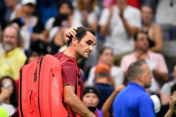 Roger Federer of Switzerland walks off the court after his loss to John Millman