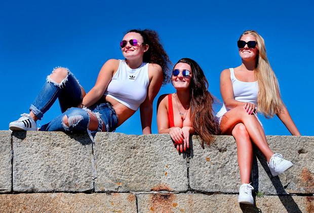 Basking: Chelsie and Dana Crowe with Lauren Mills, all from Coolock, soak up the sun on Howth Pier in late May. Photo: Steve Humphreys