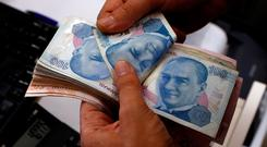 A money changer counts Turkish lira banknotes at a currency exchange office in Istanbul, Turkey. Photo: Reuters