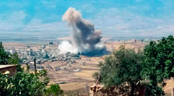 Smoke rising over buildings hit by air strikes. Photo: AP