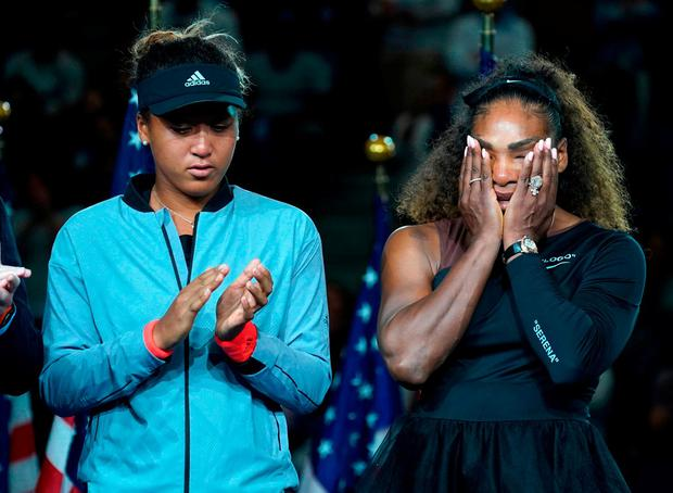 Naomi Osaka stands beside the defeated Serena Williams after Saturday's night's final. Photo: Timothy A. Clary/AFP/Getty Images