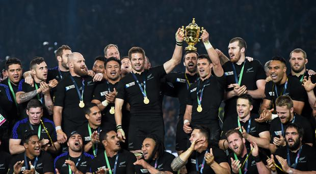 Zealand captain Richie McCaw and Dan Carter, right, lift the Webb Ellis Cup in 2015