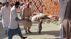 Afghan men carry an injured man to a hospital after the suicide attack in Nangarhar province. Photo: Reuters