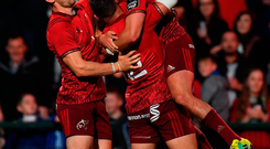 Joey Carbery of Munster is congratulated by team-mates Darren Sweetnam, left, and Dan Goggin