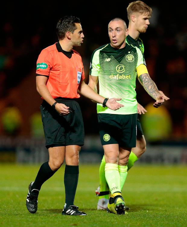 Celtic's Scott Brown (right) speaks with referee Andrew Dallas