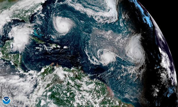 This enhanced satellite image made available by NOAA shows Tropical Storm Florence, upper left, in the Atlantic Ocean on Tuesday, Sept. 1, 2018 at 3:30 p.m. EDT. At center is Tropical Storm Isaac and at right is Hurricane Helene. (NOAA via AP)