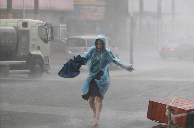 A woman runs in the rainstorm as Typhoon Mangkhut approaches, in Shenzhen, China September 16, 2018. REUTERS/Jason Lee