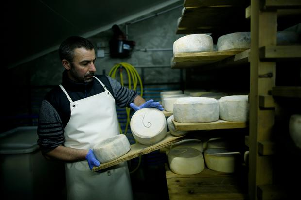 FILE PHOTO: French farmer Cedric Briand inspects cheese that ages in a storage room at a farm in Plesse, France February 21, 2017. REUTERS/Stephane Mahe/File Photo