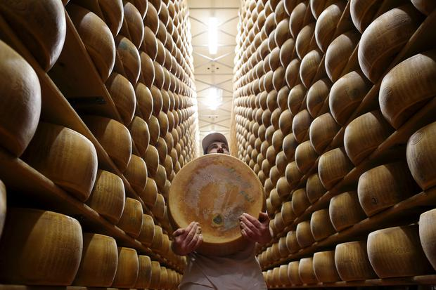 FILE PHOTO: Worker carries fresh Parmesan wheel off storehouse shelf a 4 Madonne Caseificio dell'Emilia dairy cooperative in Modena, Italy, February 16, 2016. REUTERS/Alessandro Bianchi/File Photo