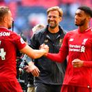 Liverpool manager Juergen Klopp celebrates with Jordan Henderson and Joe Gomez after the match